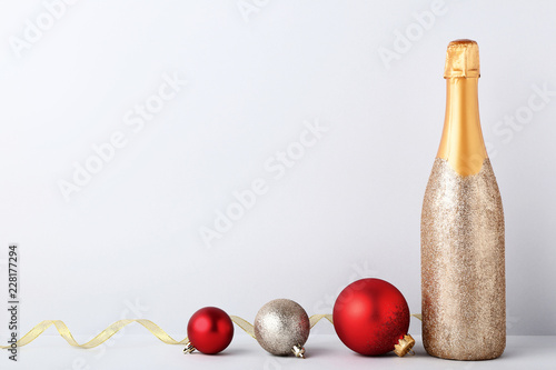 Fotografie, Obraz  Decorated champagne bottle with christmas baubles on grey background