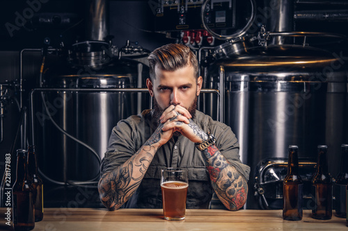 Fotografía  Portrait of a pensive tattooed hipster male with stylish beard and hair in the shirt in indie brewery