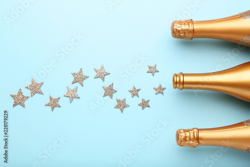 Decorated champagne bottles with stars on blue background