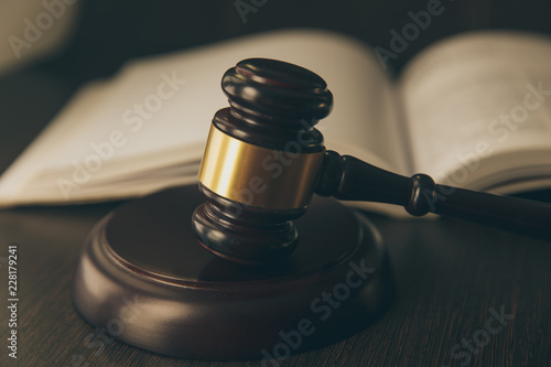 Law concept - Open law book with a wooden judges gavel on table in a courtroom or law enforcement office on blue background Wallpaper Mural