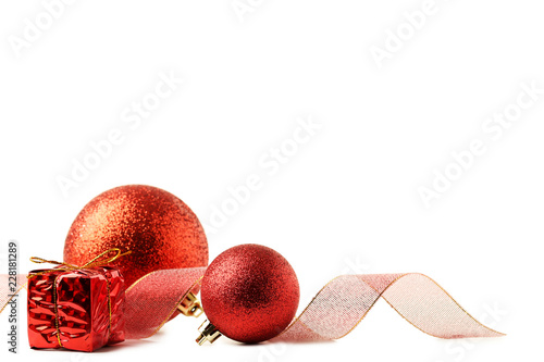 Foto  Christmas baubles with ribbon and gift box isolated on white