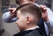 Barber making hairstyle to a Caucasian boy using scissors and hairbrush.