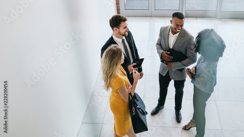 Corporate professionals having casual meeting in office lobby Canvas Print