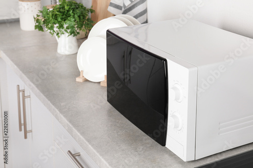 Modern microwave oven on table in kitchen