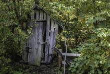 Old Wooden Corn Crib Shed. Abandoned Old Wooden Shed With Antique Farm Tools Being Overtaken By The Forest.