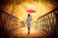 Young Beautiful Brunette Girl In Blue Coat With Umbrella Walking In The Autumn Park