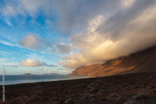 mountain with a cap of clouds on the ocean at sunset