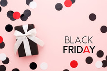 Black Friday Card. Black Gift Box With White Bow And Confetti On Pink Background. Top View, Copy Space, Minimal.