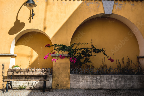 Typical yellow old building with bench and lantern in a quiet yard of Arbus, Sardinia, Italy, at lunchtime Canvas Print
