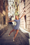 Fototapeta Uliczki - Beautiful young woman with blond hair is happy and flying through Cagliari downtown narrow streets in Sardinia, Italy. She is tanned and has striped dress.