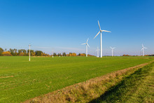 Wind Turbines Among A Green Field On A Sunny Autumn Day
