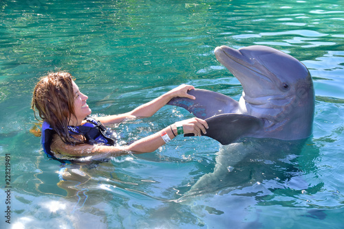 Fotografia, Obraz Young girl playing with dolphin in Xel-ha park, Rivera Maya, Mexico