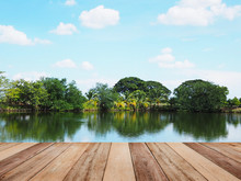 Wooden Table Top Over Blurry Background Of Fishing Pond With Reflection Of Blue Sky.