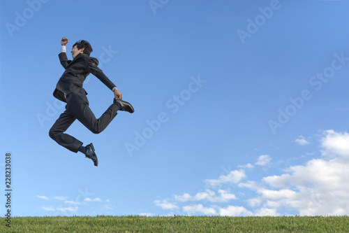 Valokuva  青空をバックに空中を走るスーツ姿の若いビジネスマン1人。元気・健康・発展・挑戦イメージ