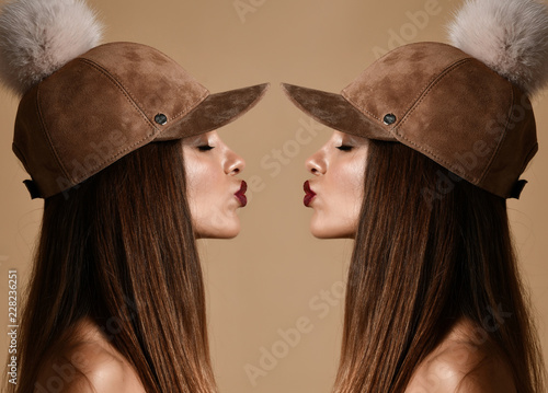 Photo Woman in winter suede pompon hat cap double art composition with closed eyes kis