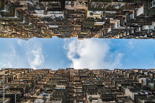 Photo  Tall skyscrapers towering above, looking toward the blue sky, crowded, dystopian