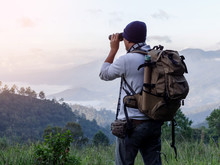 Young Man With Backpack And Holding A Binoculars Looking On Top Of Mountain