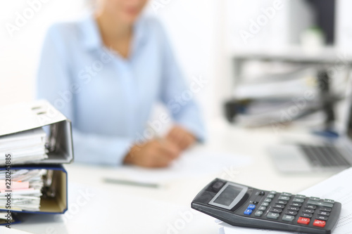 Fototapety, obrazy: Calculator and binders with papers are waiting to be processed by business woman or bookkeeper back in blur. Internal Audit and tax concept