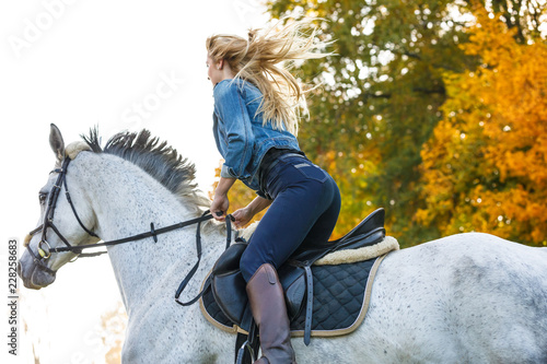 Woman horse riding in park Fotobehang