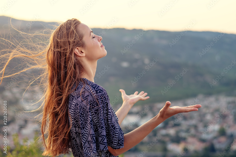 Fototapeta Christian worship and praise. A young woman with her hands raised in worship and praise to god.