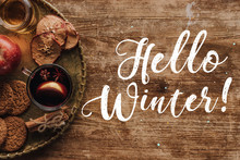 Top View Of Mulled Wine In Cup And Greeting Hello Winter On Wooden Tabletop, Christmas Concept
