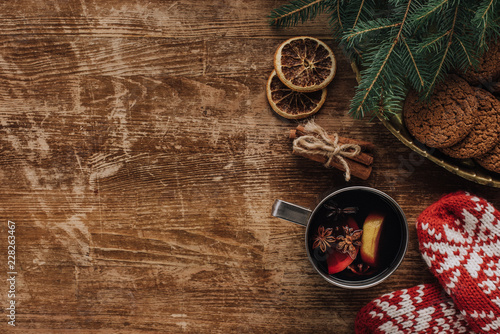 Foto op Canvas Kerstmis elevated view of mulled wine in cup, mittens and cookies on wooden tabletop, christmas concept