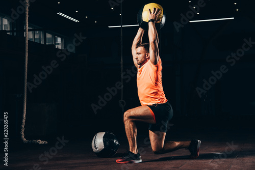 handsome fit sportsman performing lunge with medicine ball overhead in dark gym Wallpaper Mural