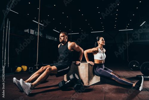 Fototapeta premium athletic sportsman and sportswoman exercising on cube together in dark gym