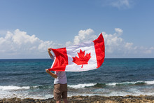 The Man Is A Guy A Tourist Traveler Holds A Canadian Flag Over His Head That Develops In The Wind. Surrounded By The Beach And The Blue Ocean On The Shore. Wooden Jetty And Good Sunny Summer Weather.