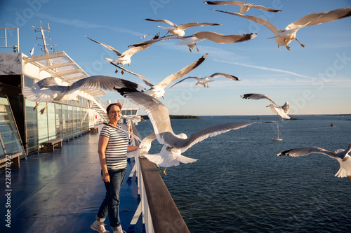Fotografía Older woman watching seagulls flying