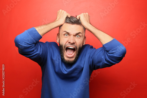Portrait of aggressive man on color background