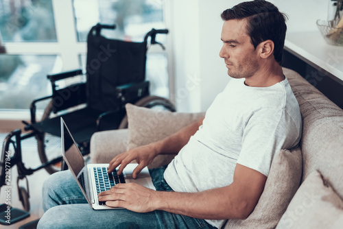 Photo  Disabled Man Sitting on Sofa and Typing on Lap