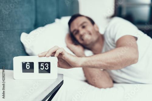 Valokuva  Cheerful Man Awakes and Pull Alarm Off in Morning