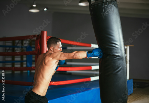 Male boxer hitting punching bag at a boxing studio