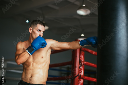 Fototapeta Male boxer hitting punching bag at a boxing studio