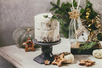 Fototapeta Autumn homemade white naked cake decorated by rated by star cookie and green thuja branches on cake stand fir tree, cookies, xmas decor above on white marble table. grey wall at background.