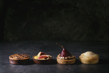 Variety Of Sweet Tartlets With Chocolate, Caramel, Pears, Figs In Row On Black Texture Table.