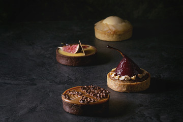 Fototapeta Variety of sweet tartlets with chocolate, caramel, pears, figs on black texture table.