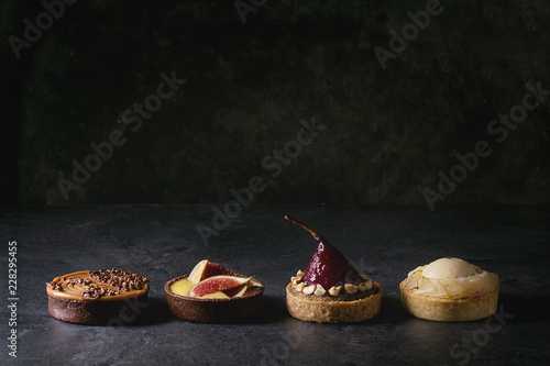 Fotografia Variety of sweet tartlets with chocolate, caramel, pears, figs in row on black texture table