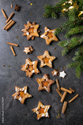Homemade Christmas New year star shape sugar caramel cookies with frosting and orange citrus jam, cinnamon sticks and anise over black texture background with fir branches. Flat lay, space