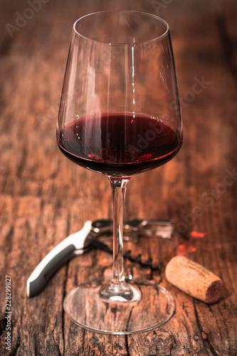 calice di vino rosso su tavolo di legno con cavatappi e tappo di sughero