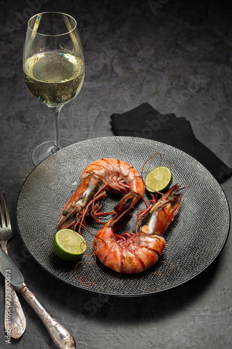 Two jumbo shrimps with lime for dinner on dark plate and glass of vine. Food background. Top view. Vertical composition.