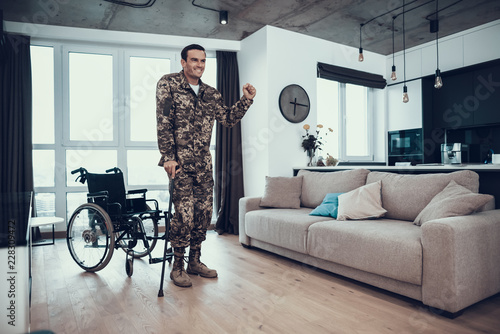 Valokuva  Disabled Soldier Leans on Crutch near Wheelchair