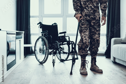 Fotografie, Obraz  Military Legs Leaning on Crutch near Wheelchair
