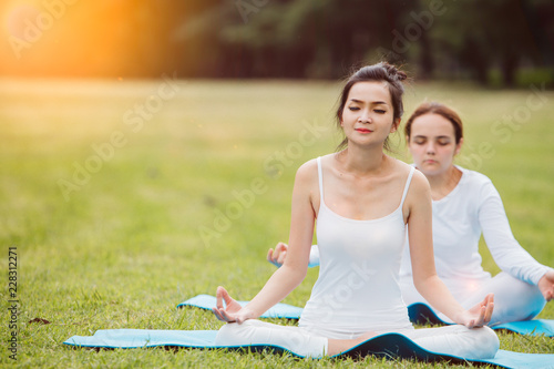 Woman doing yoga on the park - beautiful lights.relax in nature on the park .
