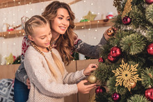Happy Mother And Daughter In Sweaters Decorating Christmas Tree With Baubles At Home