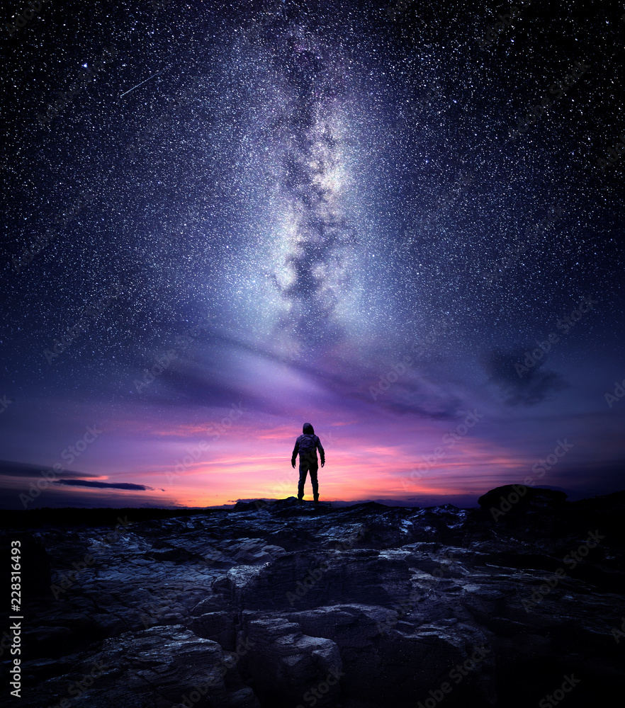 Fototapety, obrazy: Night time long exposure landscape photography. A man standing in a high place looking up in wonder to the Milky Way galaxy, photo composite.