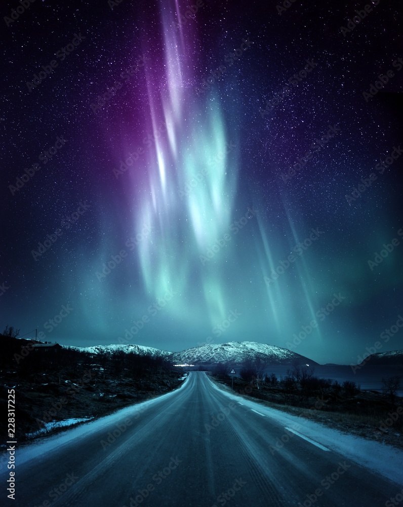 Fototapeta A quite road in Norway with a spectacular Northern Light Aurora display lighting up the night sky above the mountains. A popular destination within the arctic circle for hunting the Northern Lights.