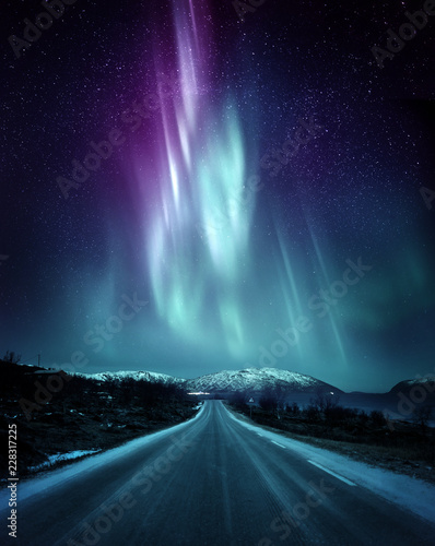 Foto auf Gartenposter Nordlicht A quite road in Norway with a spectacular Northern Light Aurora display lighting up the night sky above the mountains. A popular destination within the arctic circle for hunting the Northern Lights.