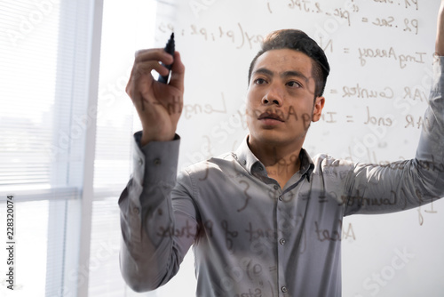 Young Asian man writing script on glass transparent board standing behind it Canvas